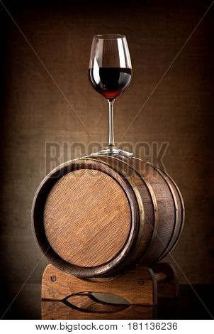 Red wine and glass with wooden barrel