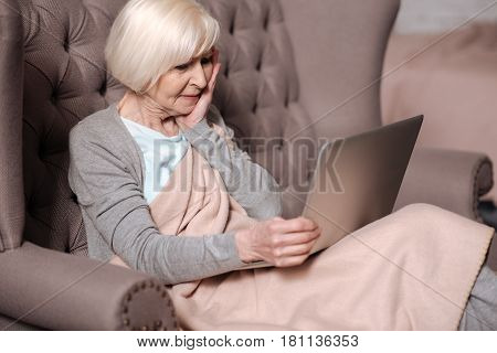 I am shocked. Side view of pretty elderly woman sitting on couch with blanket and looking impressively at laptop screen.