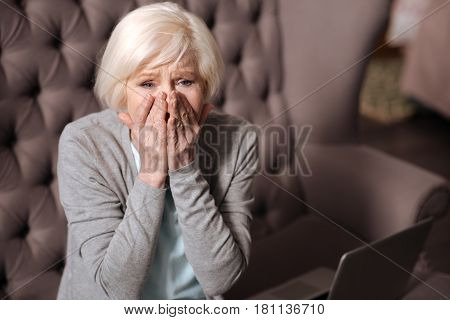 It is impossible. Close up portrait of senior woman feeling shock while sitting at home.