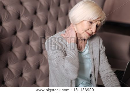 Bad spasm. Close up portrait pretty elderly woman sitting and touching her neck because of pain.