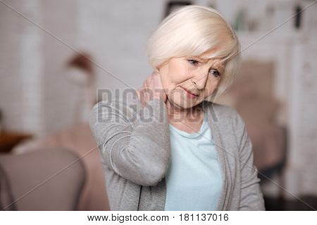 Feel bad. Close up portrait of pretty elderly lady touching her aching neck.