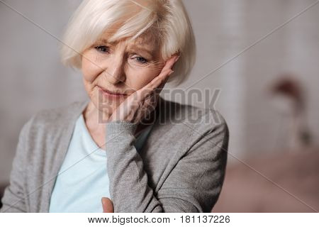 So unexpected. Close up portrait of very depressed senior lady touchig her cheeck with hand.