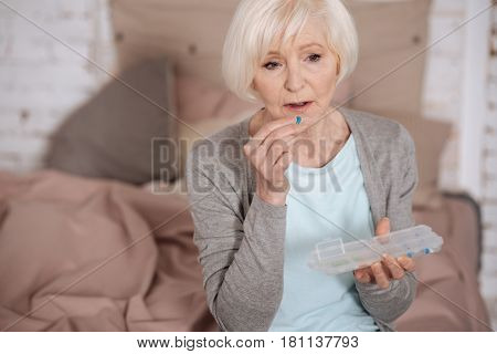 Need it. Top view of serious senior woman taking pill while sitting at home.