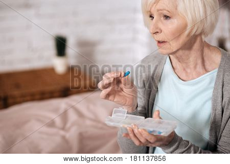 It may help. Close up side view of sad elderly lady taking pill from special case.