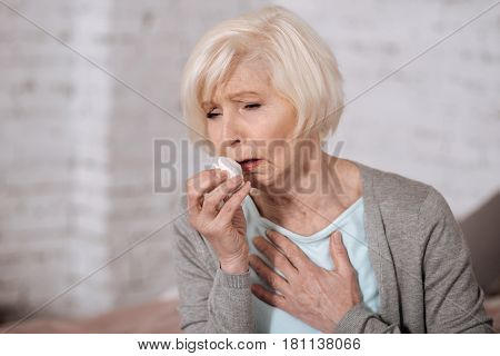 Bronchitis again. Close up of pretty aged woman holding napkin and coughing very strongly.