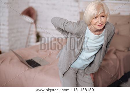 Not again. Pretty senior woman standing and feeling discomfort because of pain in back. poster