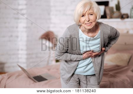 So sudden. Portrait of poor senior woman leaning forward because of strong abdominal pain.