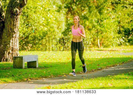 Woman runner running in summer park