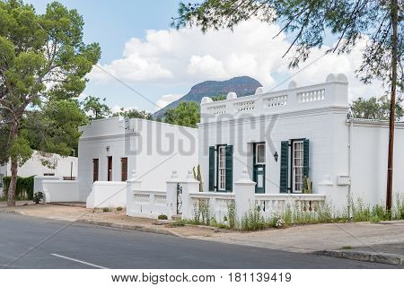 GRAAFF REINET SOUTH AFRICA - MARCH 22 2017: Historic old houses in Graaff Reinet in the Eastern Cape Province with Spandaukop visible in the back
