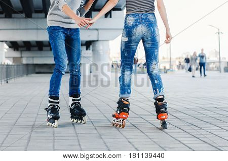 legs loving couple in jeans and rollerblading.