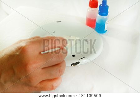 Blood sampling and analysis in a biochemical laboratory on a light background with a red ribbon.