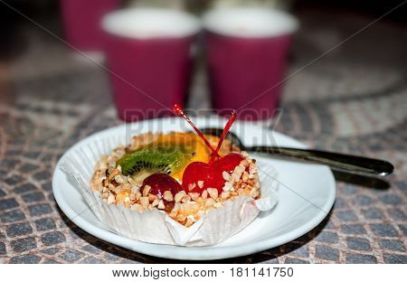cake basket with cream, decorated with slices of KIWI, pineapple and two Cherries, topped with crushed nuts , selective focus