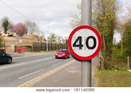 Urban 40 miles per hour speed limit sign used in the United Kingdom with defocussed traffic in the background