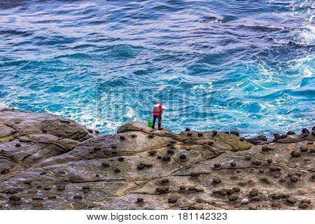 View of a fisherman fishing in the deep ocean with waves