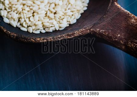 A spoon of seed seeds in a natural wooden spoon in rustic style against the background of a natural textured tree of dark color. With a wire for signing
