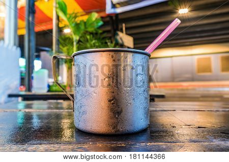 Metal cup on a table at night in Thailand