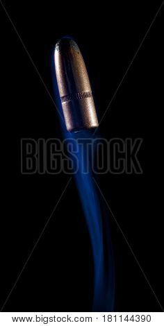 Blue smoke trailing a bullet as it goes skyward on black