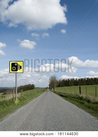 Roadside speed camera sign on single country lane through countryside and farmland