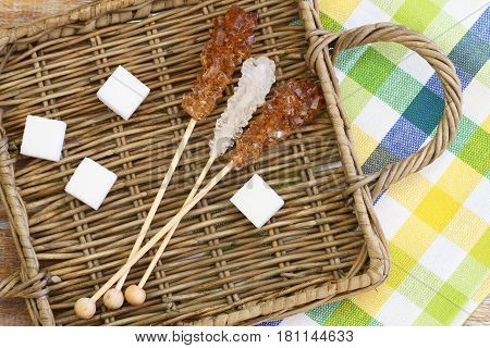 White sugar cubes and white and brown sugar sticks on wicker tray
