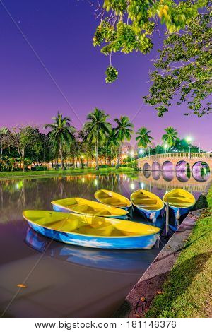 Lakeside boats with nature and bridge in Chatuchak park at night