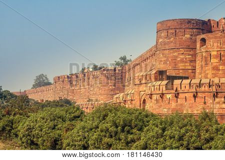 View of the Agra Fort with a blue sky and green bushes on the front. Agra Fort is a historical fort in the city of Agra in India. It is also a UNESCO World Heritage site and is about 2.5 km northwest of its more famous sister monument, the Taj Mahal