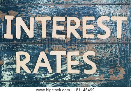 Interest rates written with wooden letters on rustic wooden surface