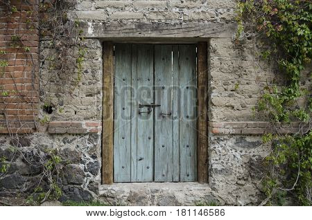VAL'QUIRICO, TLAXCALA, MEXICO- MARCH 25, 2017: Ancient door in a stone wall with plants in Val'Quirico, Tlaxcala, Mexico