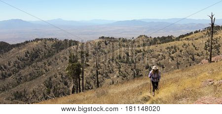 A Woman Hiker Makes Her Way Up a High Mountain Slope