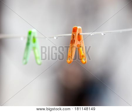 A Colorful clothespins on the clothesline outdoors .