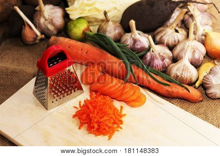 A small metal grater and carrots fresh vegetables