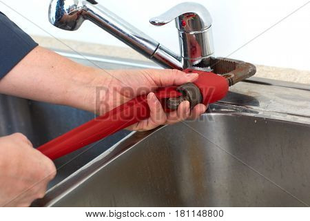 Plumber hands with wrench.