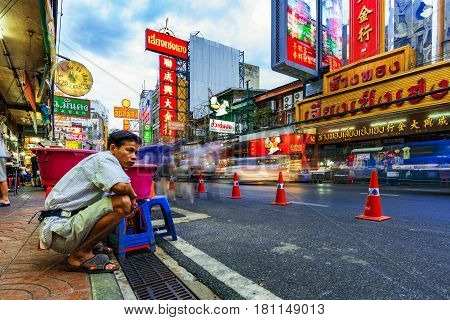 BANGKOK THAILAND - FEBRUARY 03: This is one of the main roads in Chinatown Bangkok with a street vendor waiting and watching the ongoing traffic on February 03 2017 in Bangkok