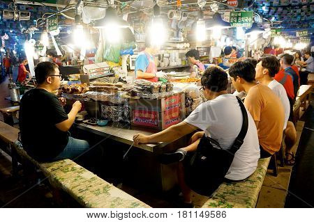 SEOUL SOUTH KOREA - MARCH 20: Korean people eating at a street food vendor in Gwangjung market on March 20 2014 in Seoul