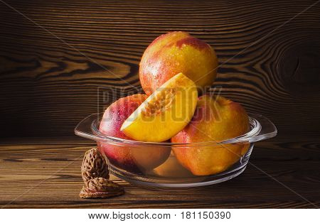 Slice of nectarine and whole fruits on a wooden table. Still life of fresh juicy nectarines.