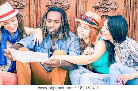 Group of multiracial happy friends looking map - Girlfriends on holiday asking direction at handsome dreads hair man sitting outdoor - Concept of girls on tour in the city