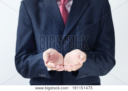 Businessman Gesturing With His Hands On Grey Background