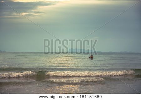man in the sea fishing during sunset with scenic sea view and sunlight shining through the clouds