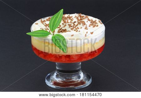 Traditional English trifle dessert on black background with copy space