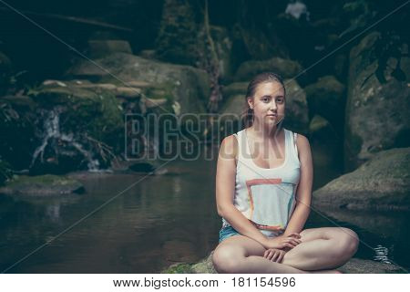 Young woman relaxing in lotus pose on the rocks nearby waterfall with mysterious Mona Lisa smile