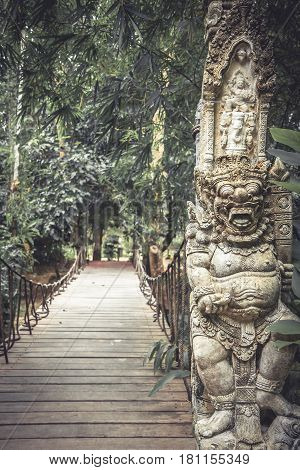 Wooden pathway leading to tropical forest with terrible statues of Asian Buddhism demon in vintage style