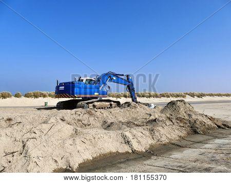Blue Excavator On Pile Of Sand