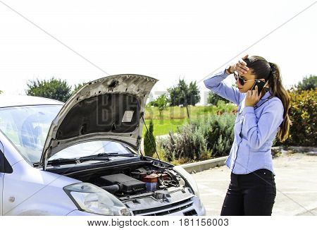 A woman gets stuck with a broken car, needs help and she hold her head because the car does not motivate
