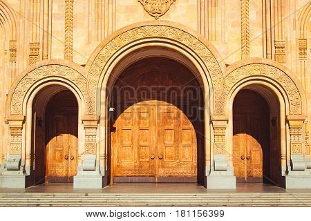 Photo of the Triple church arched wooden door. Fretted arches. Exquisite carving. Holy Trinity Cathedral Tsminda Sameba in Tbilisi, Georgia. Religious background.