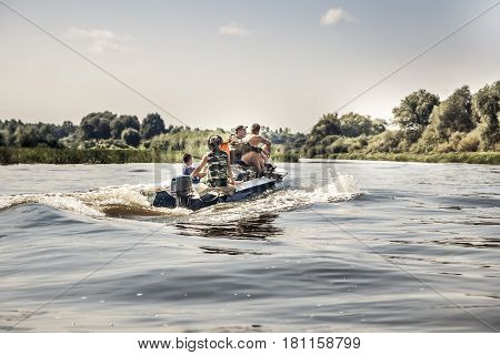 Group of men sailing on motor boat by river in summer day to the camping site during hunting season