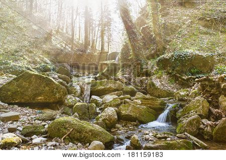 The sun's rays make their way in a gorge of the Caucasus mountains. Spring Creek - a tributary of the Mischief