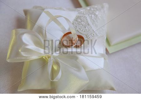 Wedding rings on a satiny fabric .