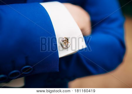 Crossed man's hands on his chest in a blue jacket. Cuff links from the watch mechanism.
