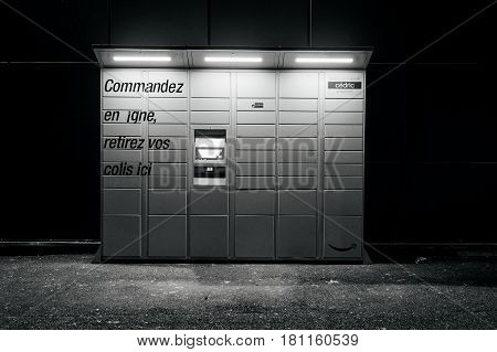 PARIS FRANCE - FEB 15 2017: Black and white night view over an Amazon locker orange delivery package locker at dusk