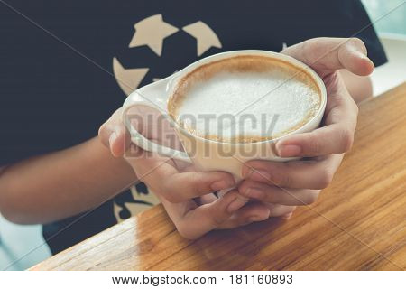 Female hands holding cup of capuchino coffee on wooden table