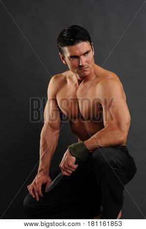 The buff man is kneeling down with a knife.